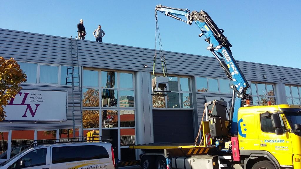 De condensor van de klimaatmachine wordt van het dak van het depot Keienbergweg 27 naar beneden getakeld.